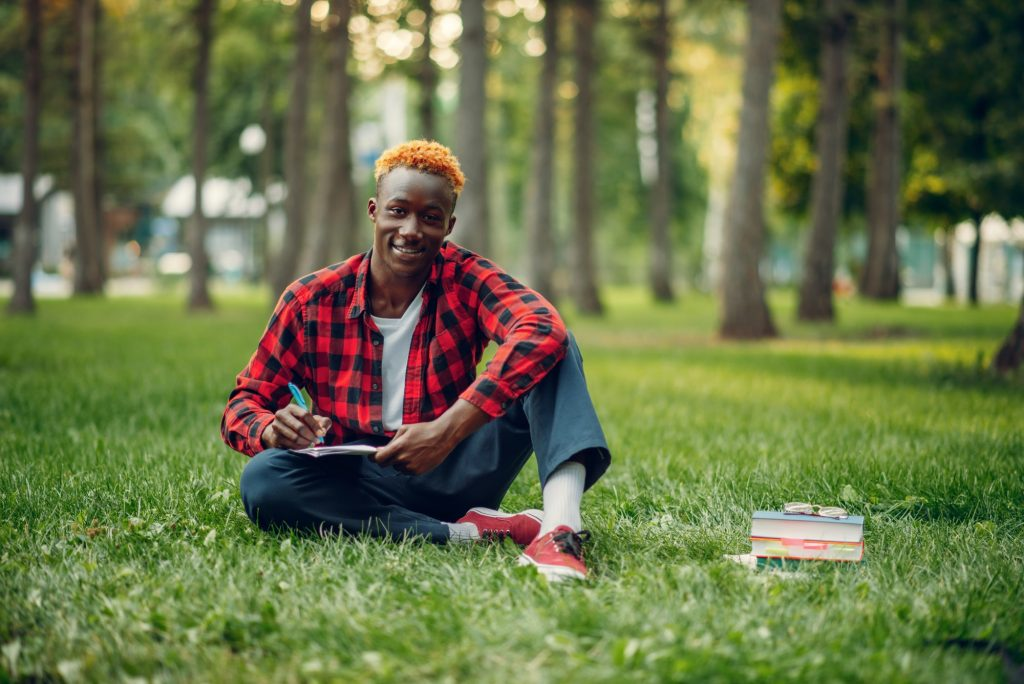 Black student writing in notebook on the grass